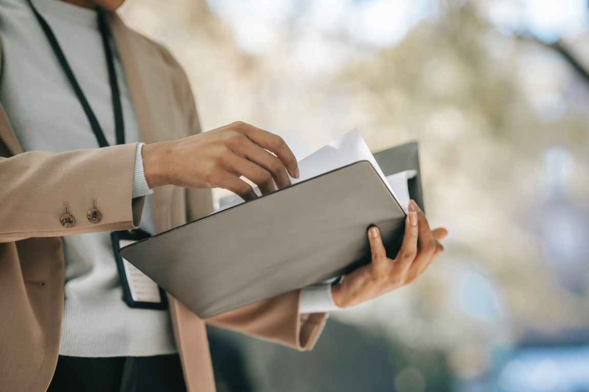 crop businesswoman with folder with documents