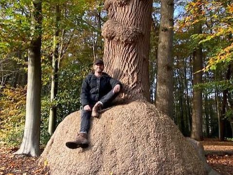 A man sitting on a giant rock forest bathing under a tree in Ansterdam