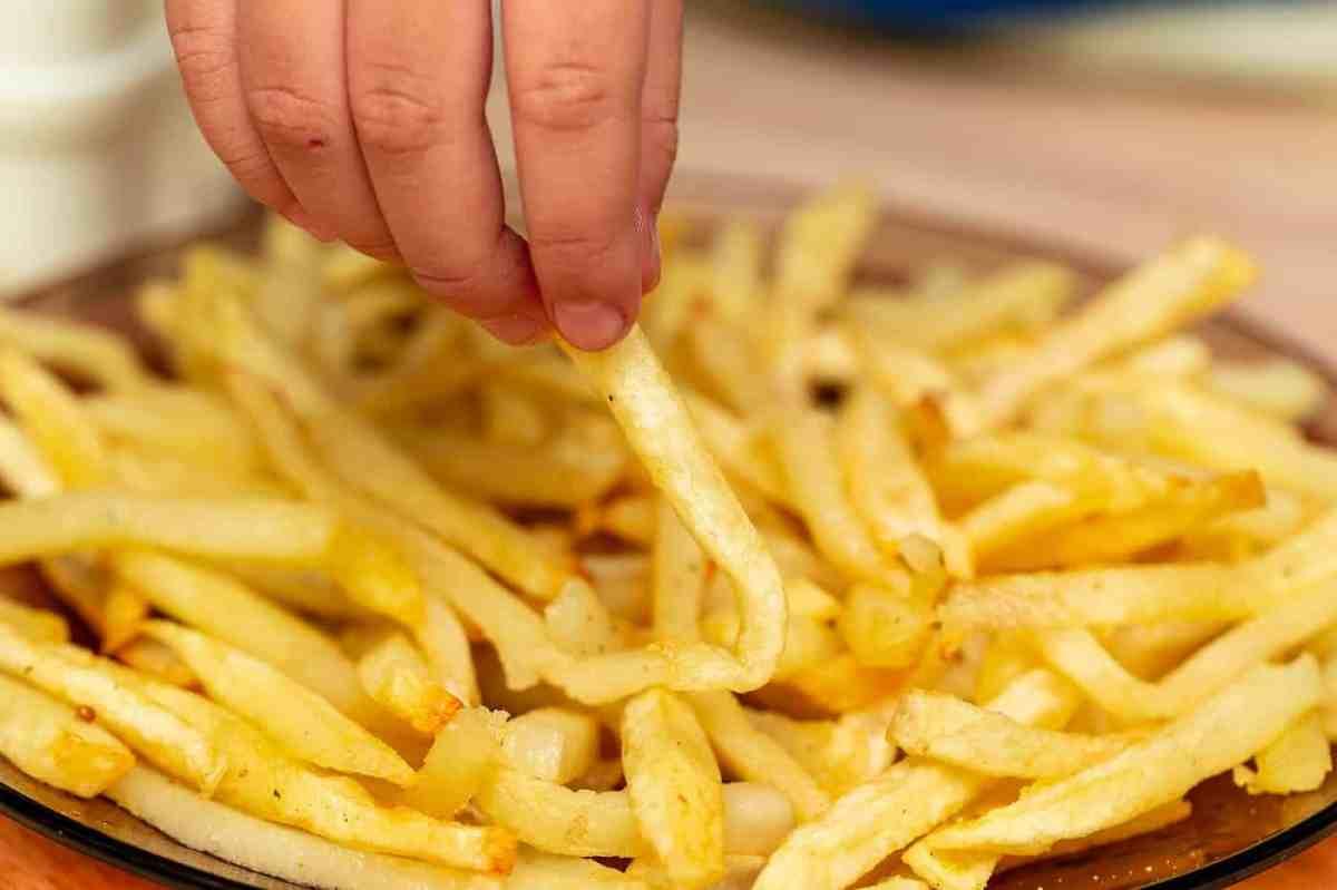 La mano de la persona busca papas fritas: comida real versus comida falsa