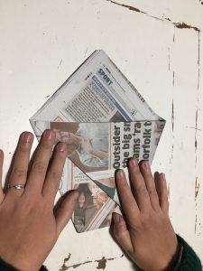 three sheets of newspaper to make one compost bin liner