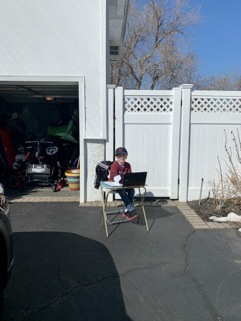 A 2nd grader doing remote learning outside on a nice day.