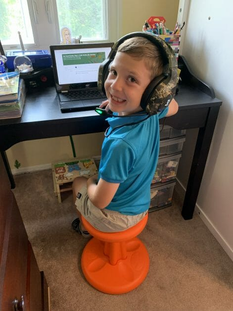 A 2nd grade boy doing remote learning in his room.