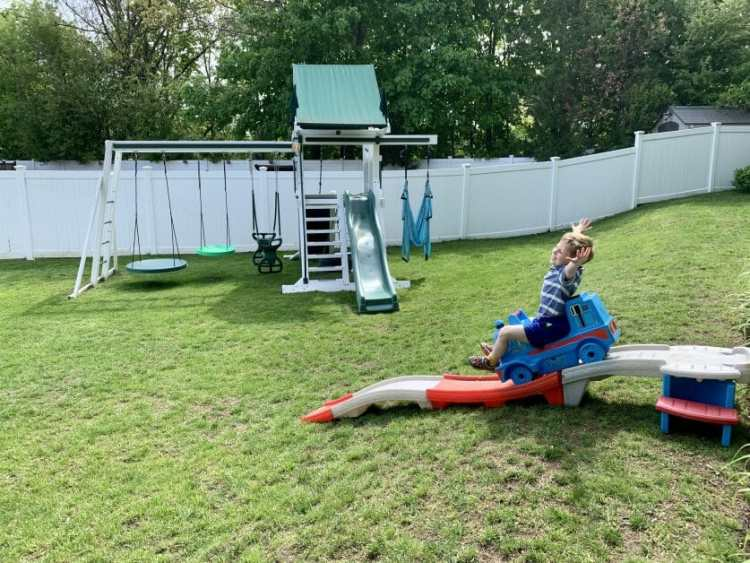 A little boy with arms up sliding down a backyard rollercoaster.