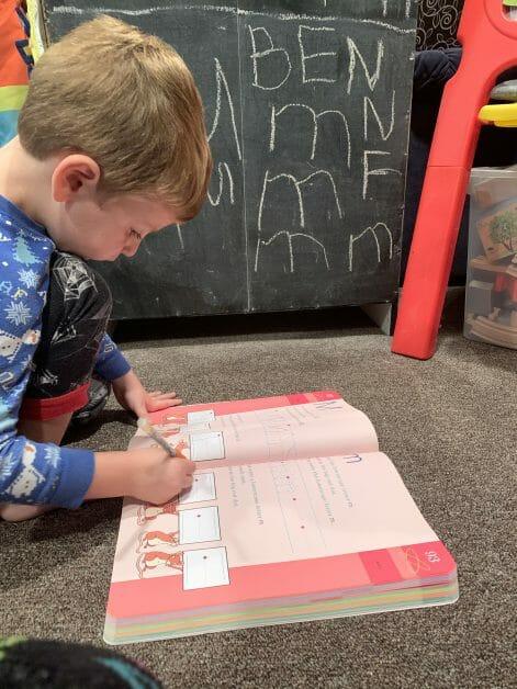 A remote Pre-K boy doing his workbook.