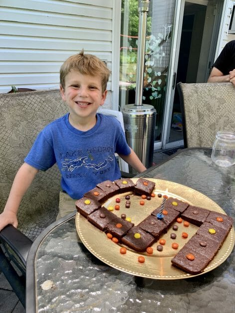 A little birthday boy with brownies in the shape of a 5