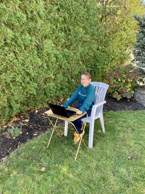 A 5th grader doing remote learning outside on a nice day.