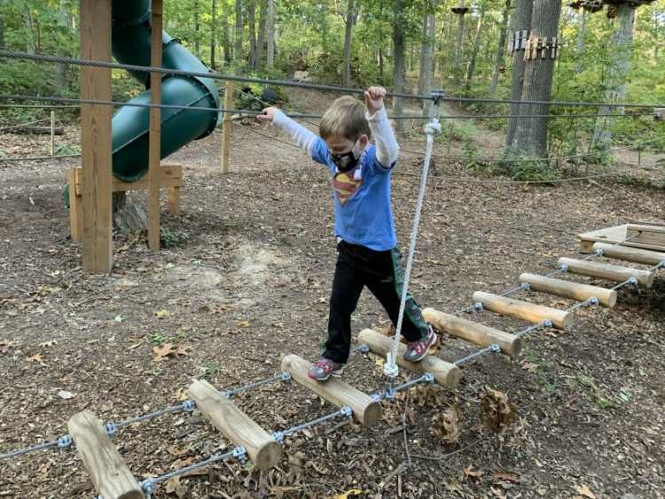 A little boy at the Adventure Playground at Adventure Park Long Island. Zipline & Ropes Courses on Long Island.