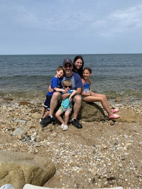 A family of 5 sitting on a rock at the water in Greenport