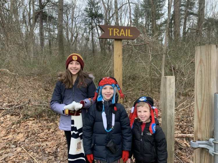 """3 kids on a hike in front of a sign that says """"trail"""""""