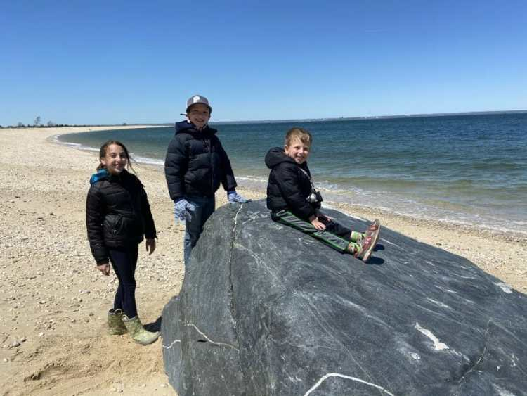3 kids sitting on a rock at Caumsett State Park