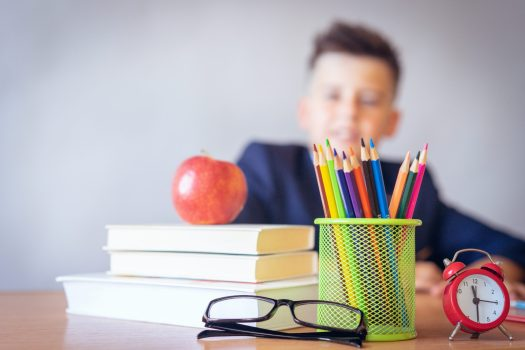 school kid looking at supplies on desk