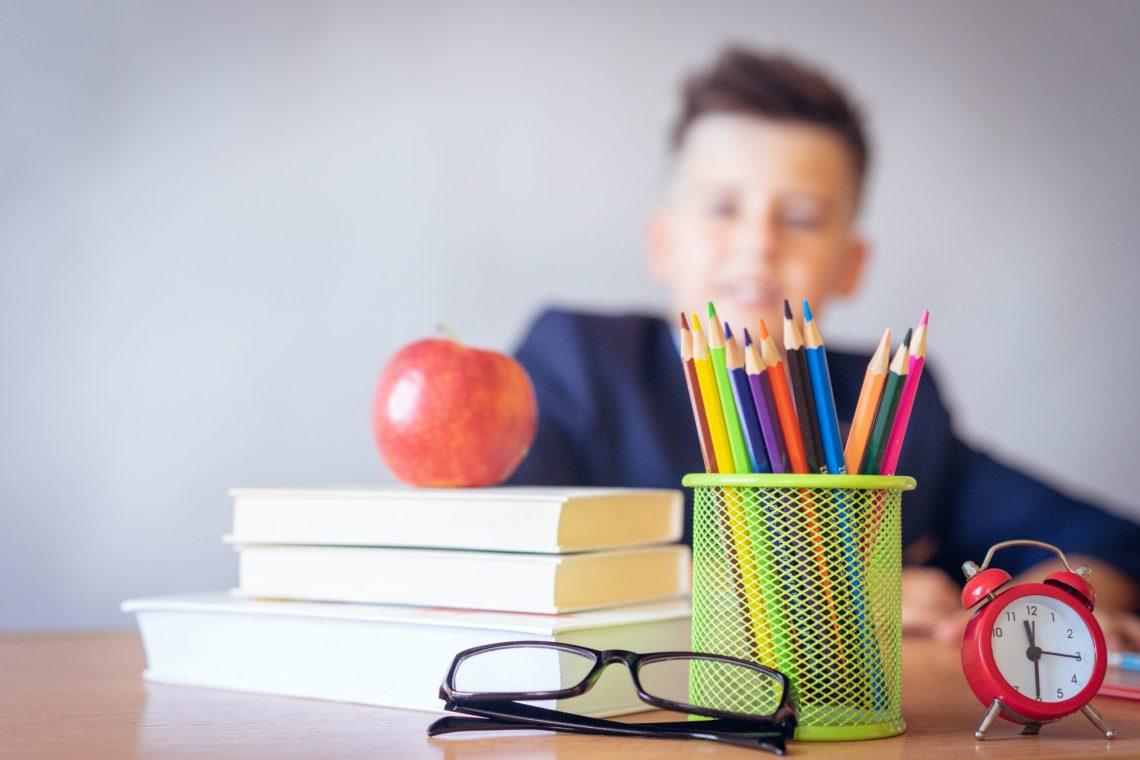 school kid looking at supplies on desk