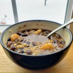 Bowl of black bean chili on a window ledge