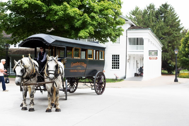 Horse and buggies roam the streets of Greenfield village.