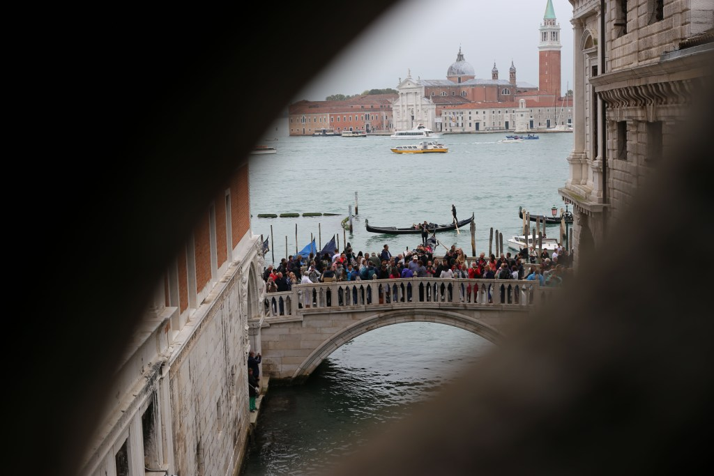 A look through the Bridge of Sighs at the waiting tourists crowding the streets of Venice. The Moment we decided to ditch any societal pressures.