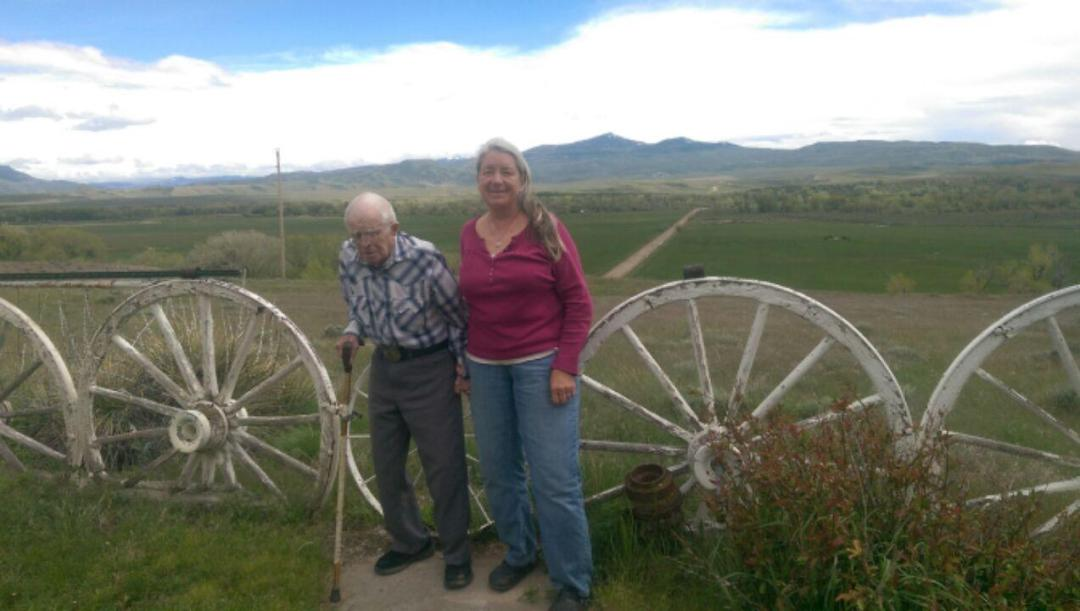 103 year old Harry Russell Jr. and his caregiver, Rose Norris, stand in Russell's backyard with a view of Baker Peak in the background. Russell's family homesteaded on the mountain.