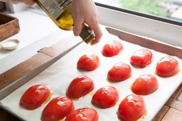 Drizzling olive oil over tomatoes