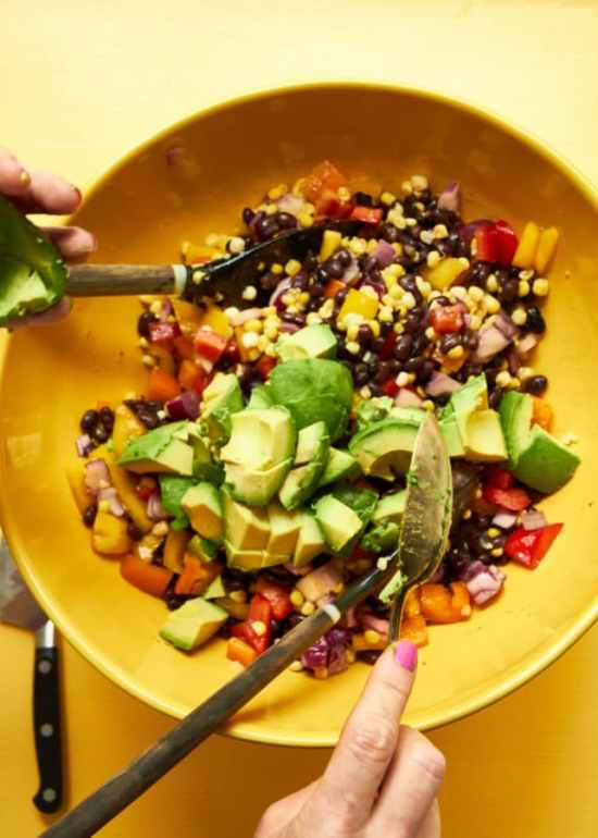 Southwest Black Bean and Corn Salad with avocado being folded in