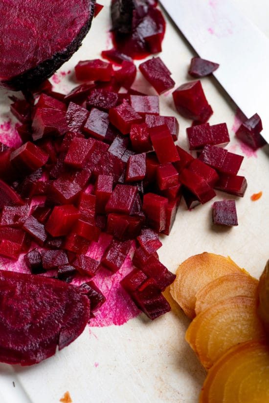 Sliced red and golden beets on a cutting board with a knife