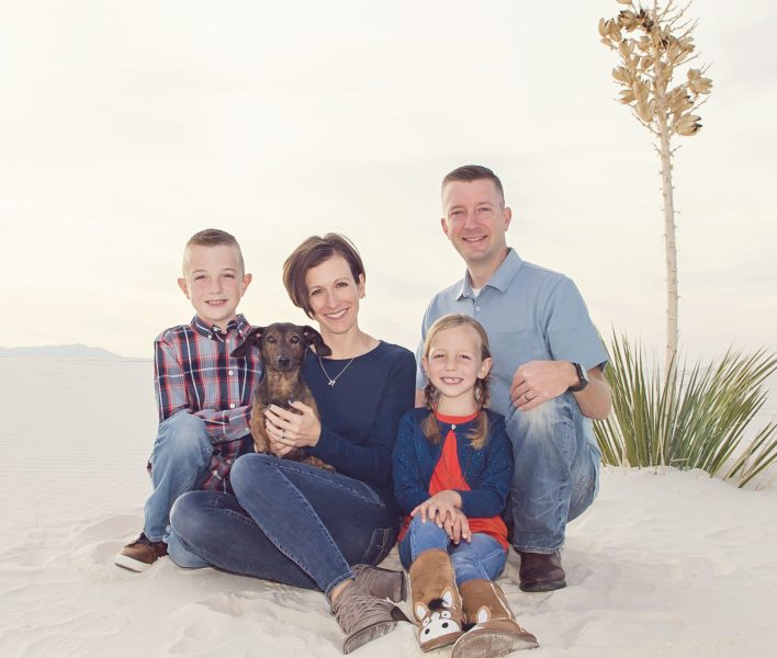 Woman, Mother, Author- Jennifer pictured with her husband, son, daughter, and family dog in a desert sand family pic
