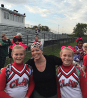 Woman, Mother, Breast Cancer Survivor- Cari pictured with scarf on her head with twin daughters in cheerleading uniforms