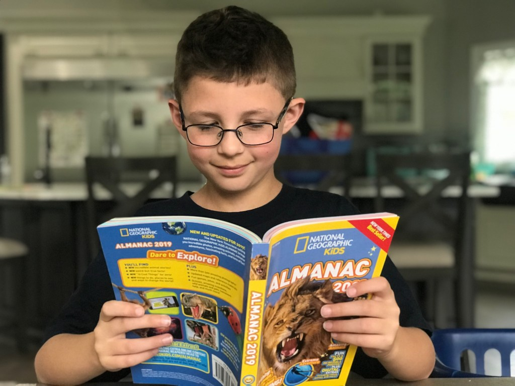 Boy reading National Geographic Kids 2019 Almanac