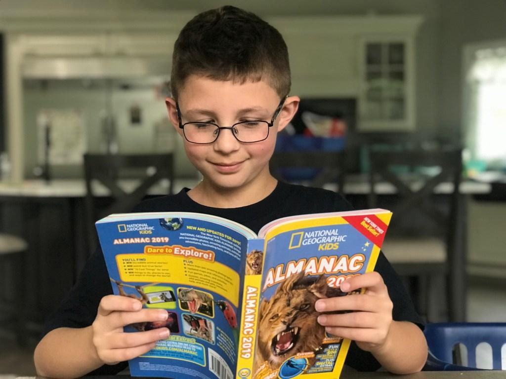 Boy reading National Geographic Kids 2019 Almanac