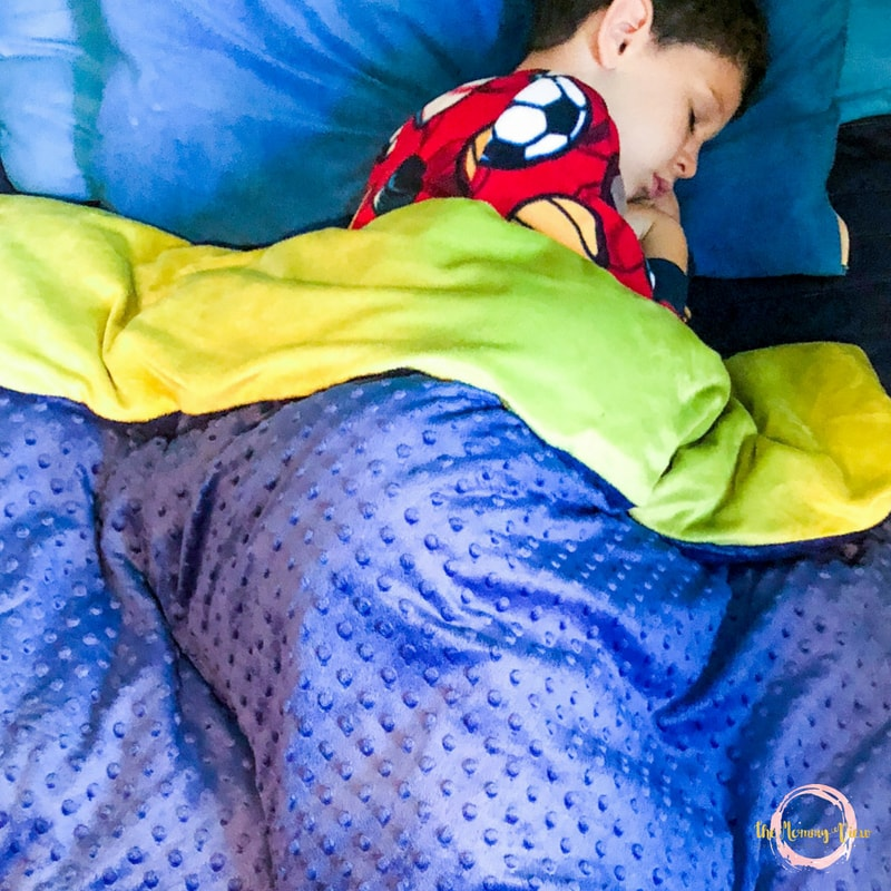 boy sleeping in bed under weighted blanket