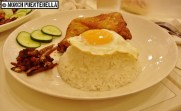 Nasi Lemak (P245): Fried chicken and coconut cream rice topped with a sunny side up egg - served with shrimp paste, cucumber slices, and anchovies.