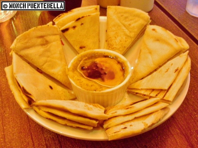 GRILLED PITA WITH HUMMUS: Middle Eastern chickpea and olive oil dip served with grilled pita bread slices.