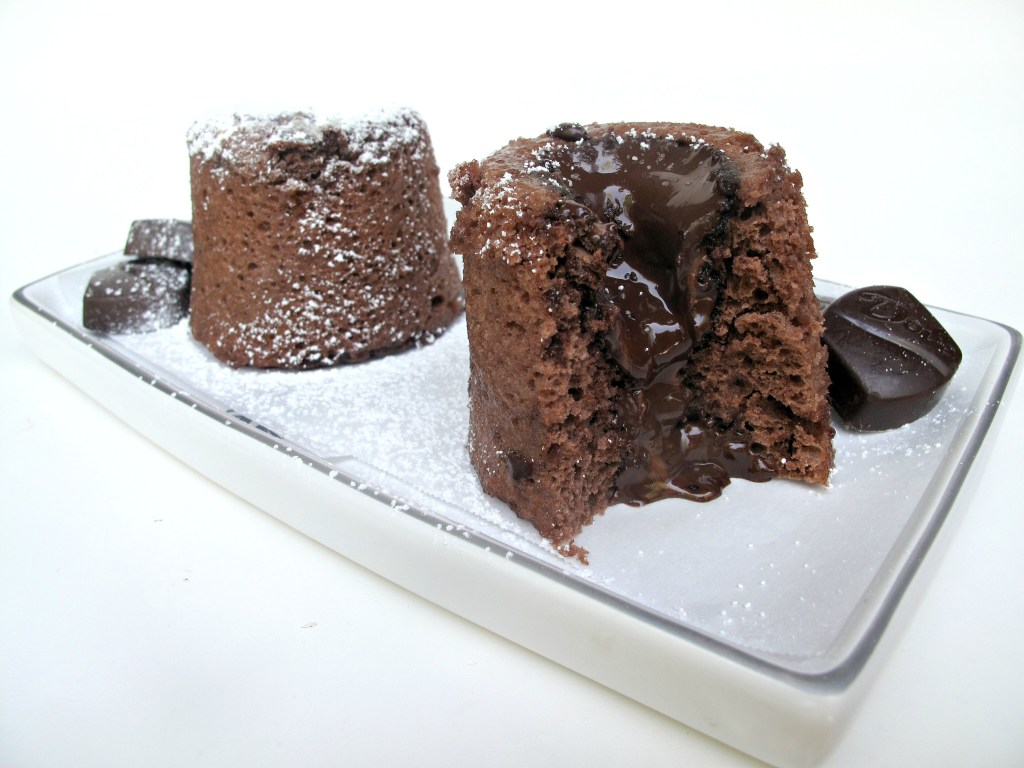 2 Molten Lava Mug Cakes on a white platter with one cut open to show melted chocolate center