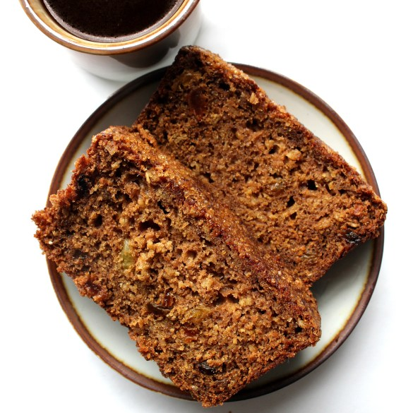 2 slices of Oatmeal Raisin Quick Bread on a small plate next to a cup of coffee