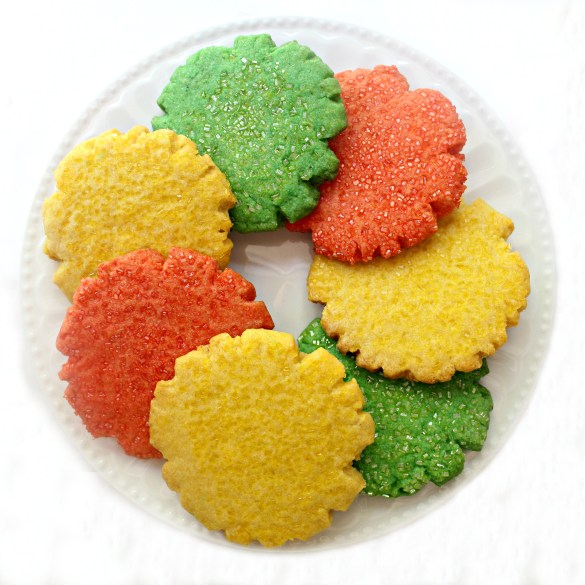 yellow, green, orange Mexican Sugar Cookies in a circle on a white plate.