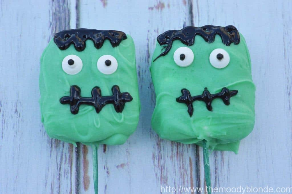 green franken-mallow halloween treats on green sticks with black hair and black mouths