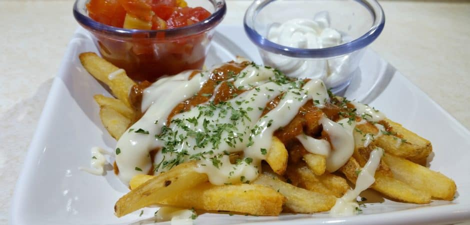 white plate of chili cheese fries with sour cream and salsa on a white countertop