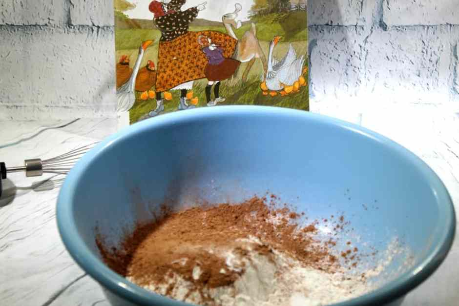 Making chocolate Thunder Cake with book in the background mixing dry ingredients in a plastic blue bowl.