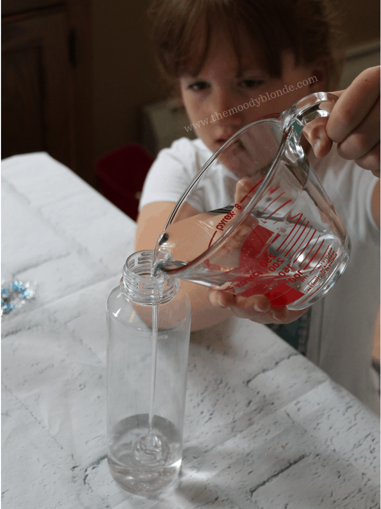child pouring ingredients into a sensory bottle voss bottle container
