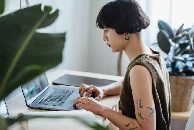 focused female working on laptop in house at table