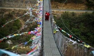 Monks commute on the Punakha Suspension bridge. Photo: Kaushik Naik