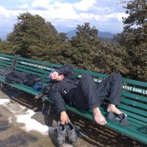 Abhishek enjoys the warmth of the sun (and dries his socks and shoes) at the Hatu Temple compound after a wet climb to the top of Hatu Peak