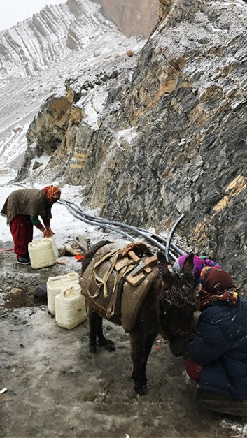 Women filling water and loading it on a donkey amidst the snow; Photo: Abhinav Kaushal