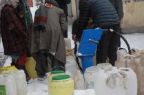 People filling water from a hand-pump, as the snowfall recedes.
