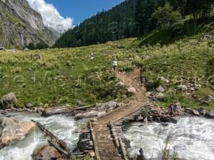 'Trek Trail Wooden Bridge' by Ameen Shaikh traces the trail over a wooden bridge on the Pin Parvati Pass trek route between Kheerganga and Tunda Bhuj.
