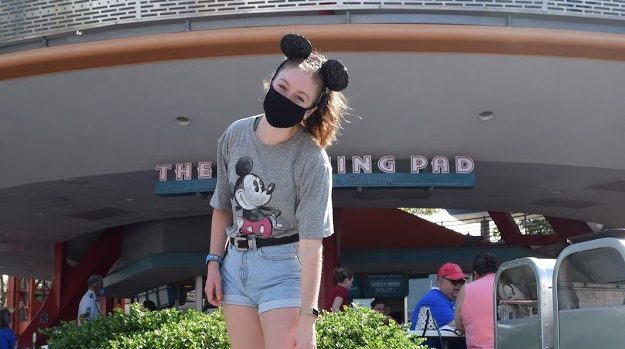 Girl standing in Tomorrowland at Disney with face mask.