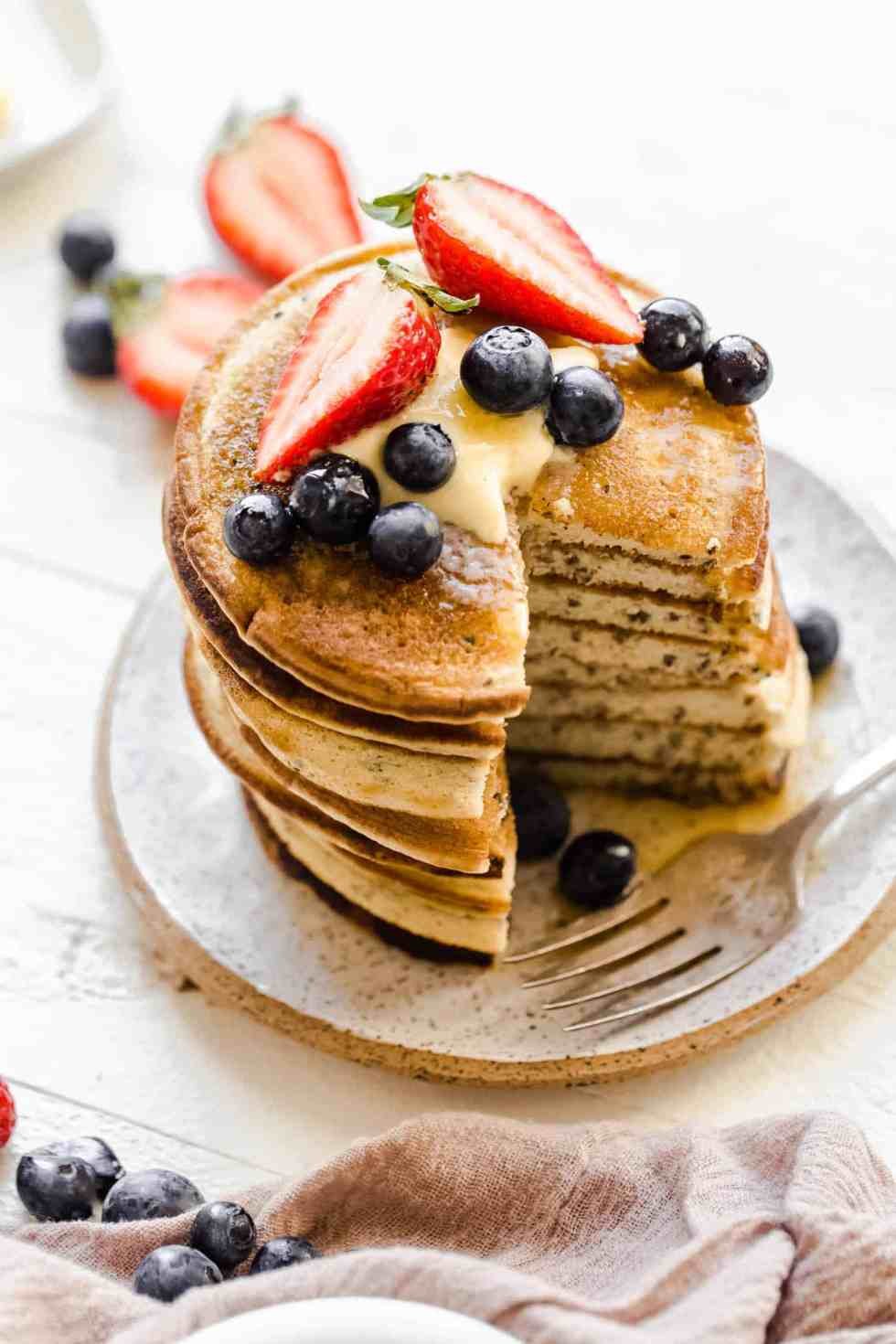 stack of several paleo pancakes on a white plate with berries