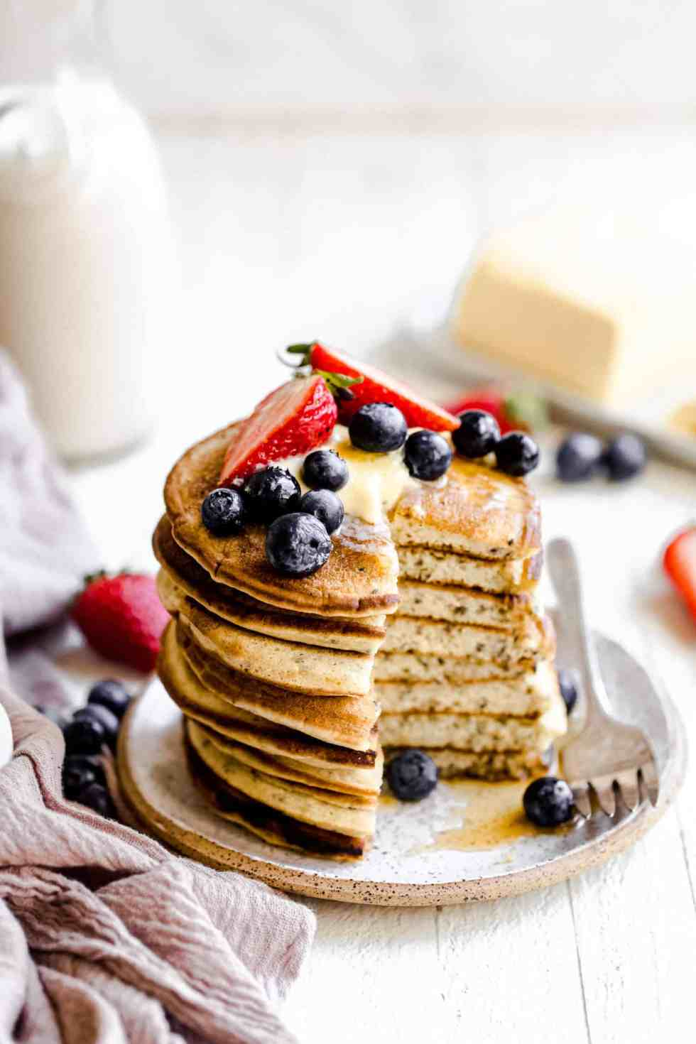 stack of pancakes with berries on top and a fork on the side