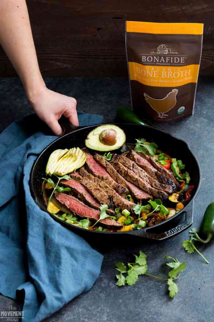 easy steak fajitas in a cast iron pan with an avocado on top