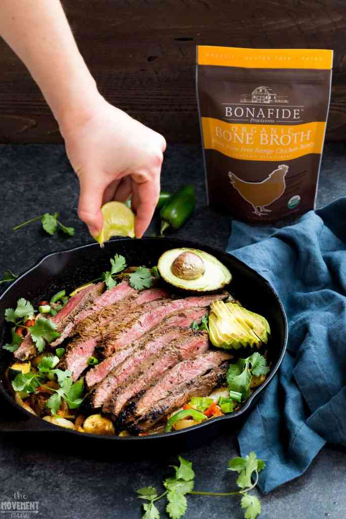 squeezing lime onto a bed of steak fajitas in a cast iron pan