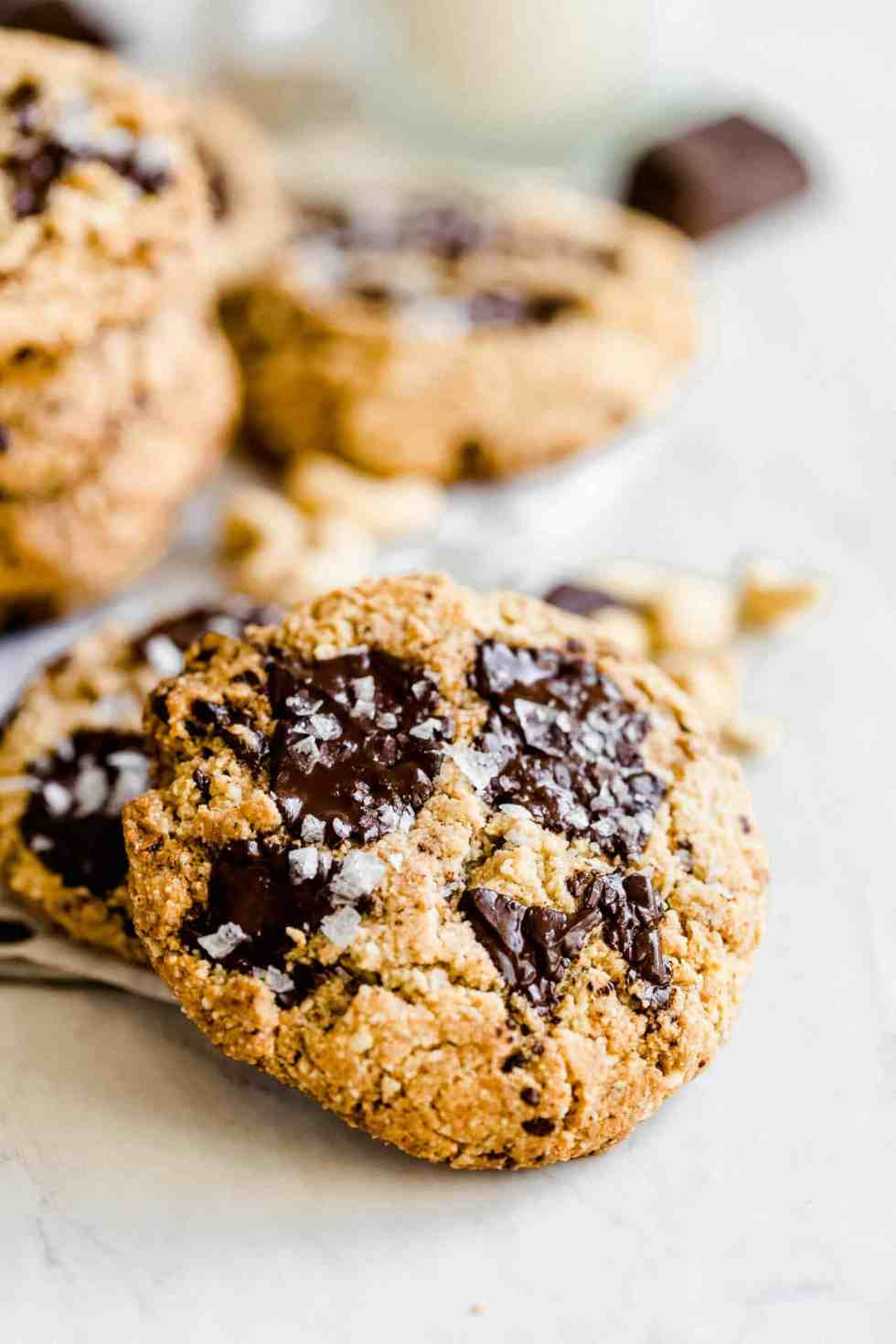 close up of gooey chocolate chip cookies on a marble board with flaked salt