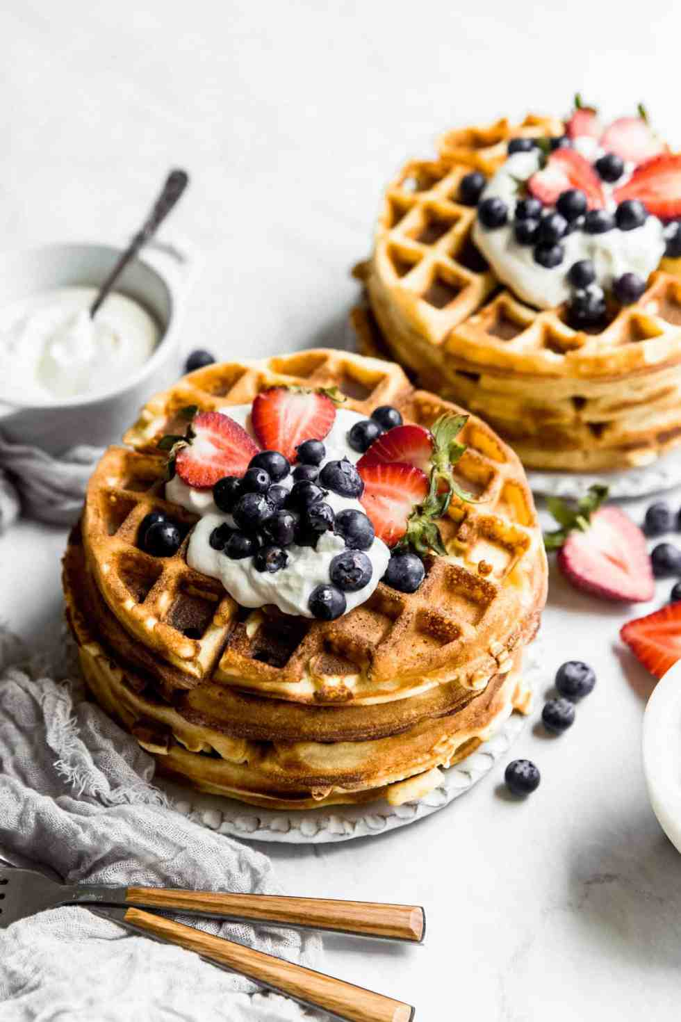 two stacks of paleo pancakes on plates with berries on top